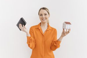 Smiling woman holding wallet and miniature house model