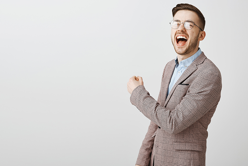 Handsome pleased caucasian male in jacket and glasses yelling from triumph and joy raising fist in victory or success gesture over gray wall.